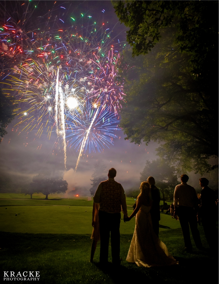 bride and groom watching fireworks with wedding guests