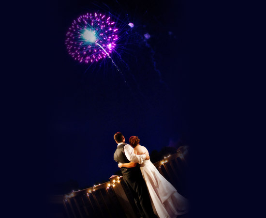 bride and groom standing watching fireworks