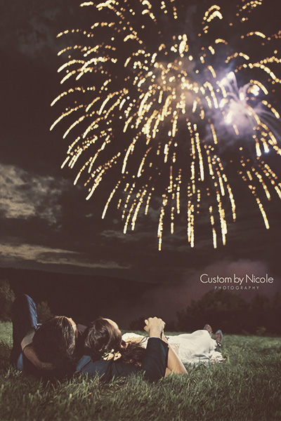 bride and groom laying down watching fireworks